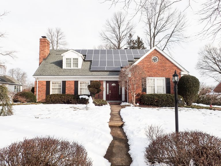 A red brick house with solar panels on roof and snowy lawn in foreground.