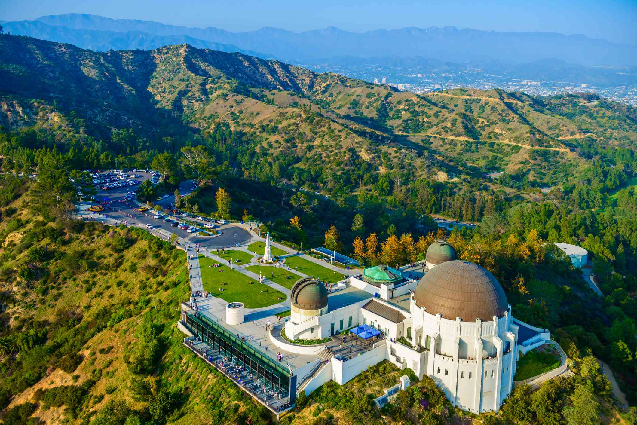 Aerial view of lush green hills of Griffith Park with the Griffith Observatory in the foreground