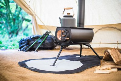 The Frontier Plus portable stove set up inside a large tent