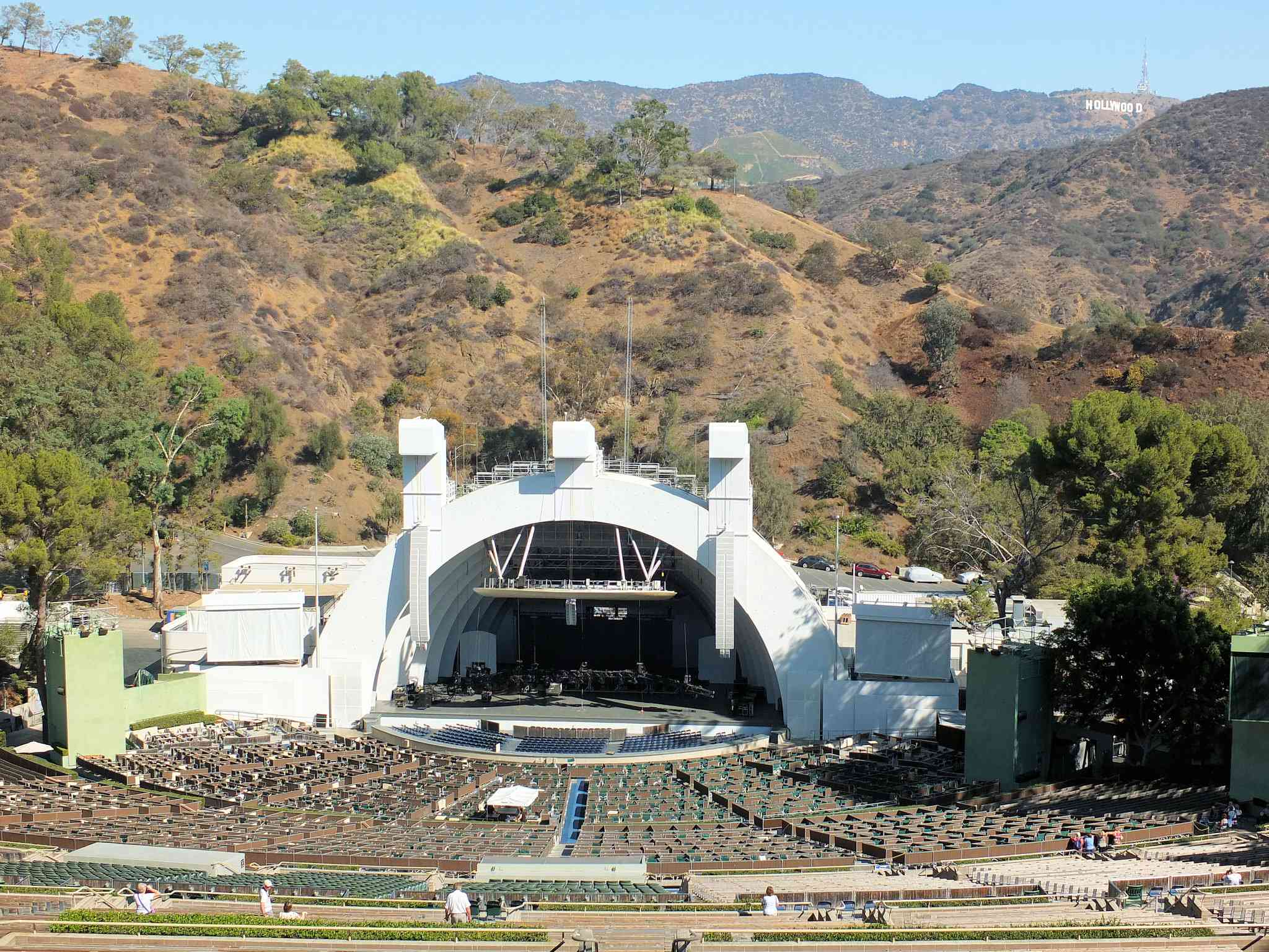 View looking down at Hollywood Bowl from top of seating area with mountains and blue sky in the background