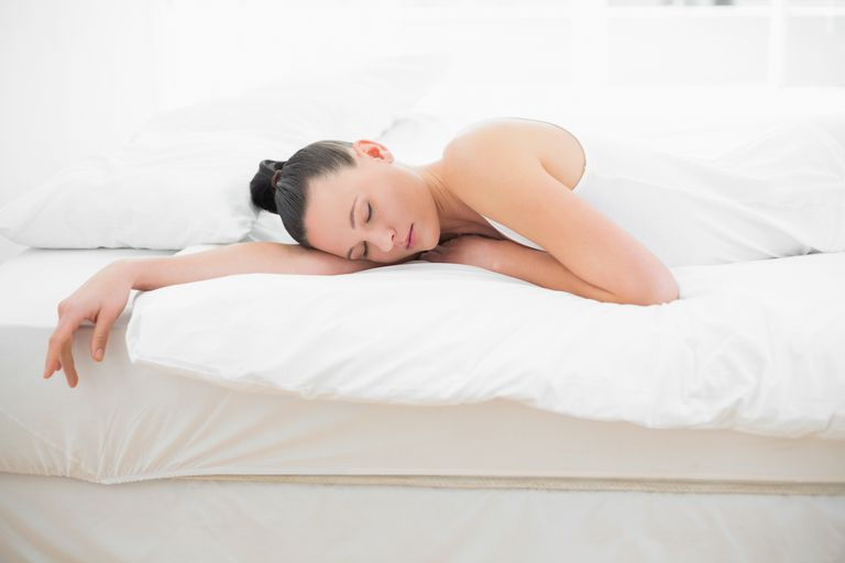 A woman sleeping in white sheets with her hair in a bun.
