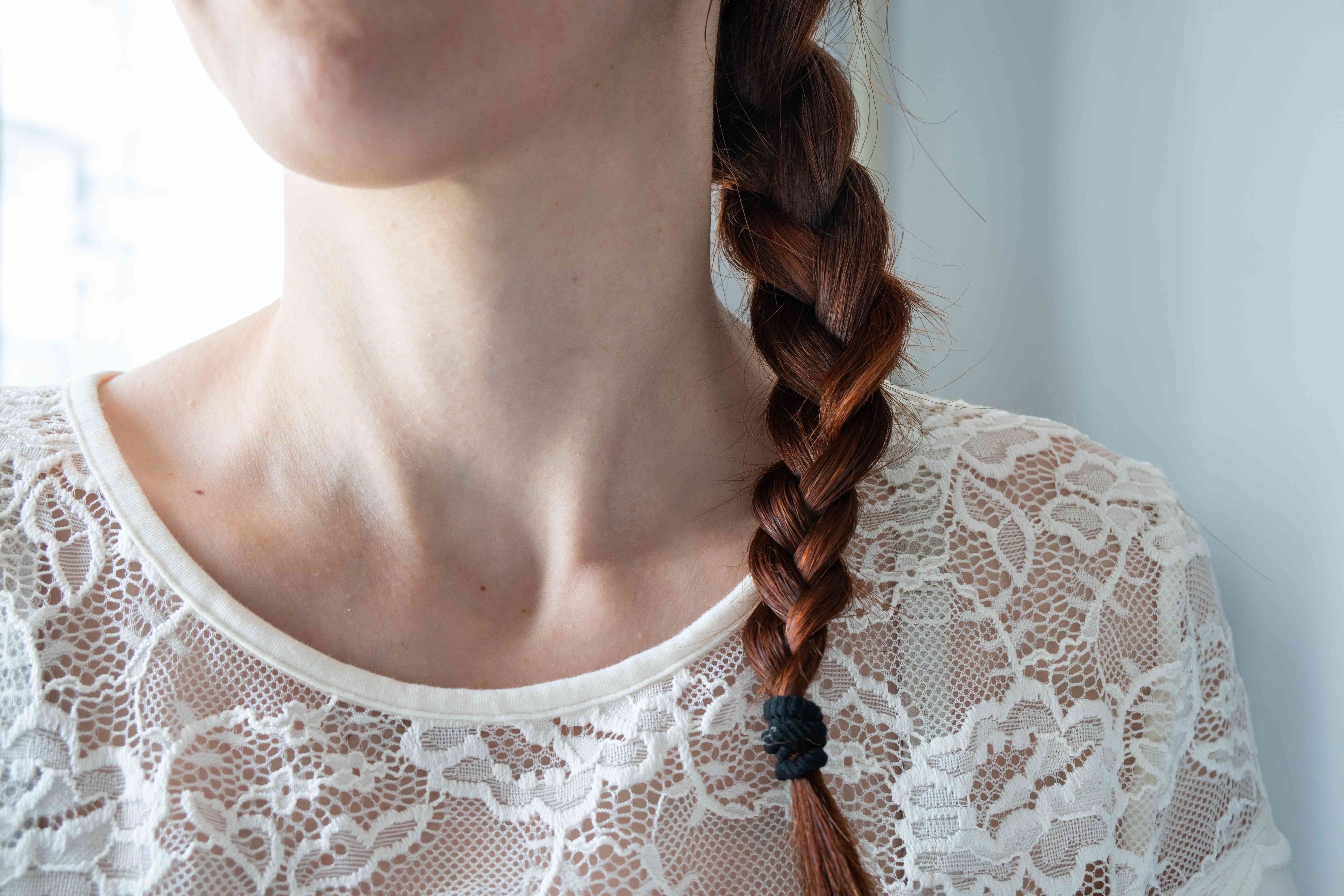close shot of woman's neck with long red braid in white lace top