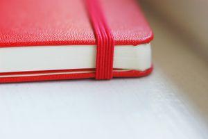A close up of a red moleskin journal.