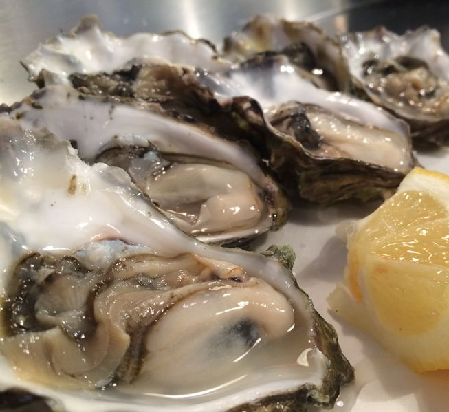 A plate of oysters with lemons