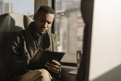 Stylish businessman taking notes while traveling by train