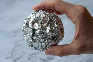 close shot of hand holding a crumpled ball of used aluminum foil