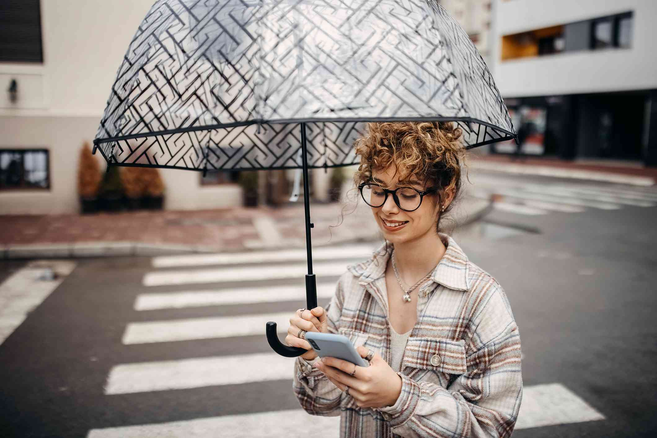 A young woman holding an umbrella crosses the road looking at her phone.