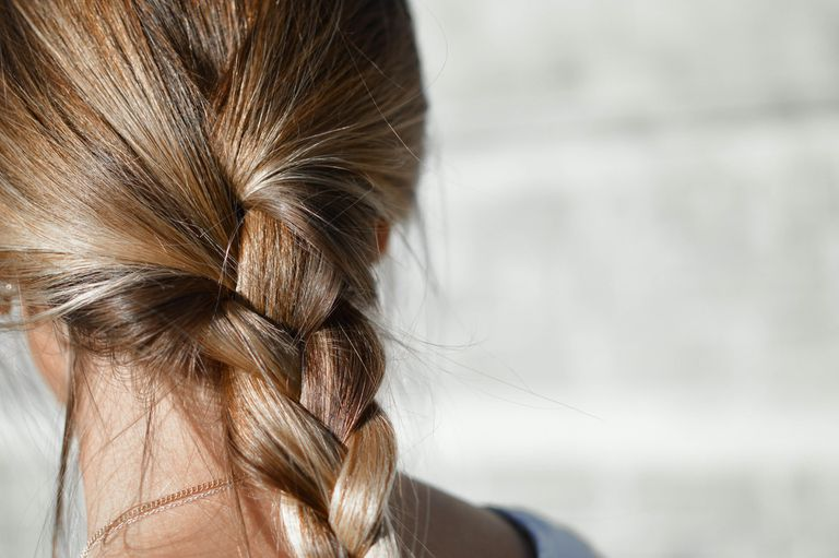 The back of a woman's head, showing braided hairstyle
