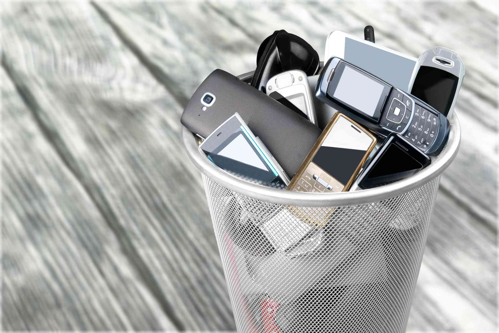 Cell phones piled up in a garbage bin.