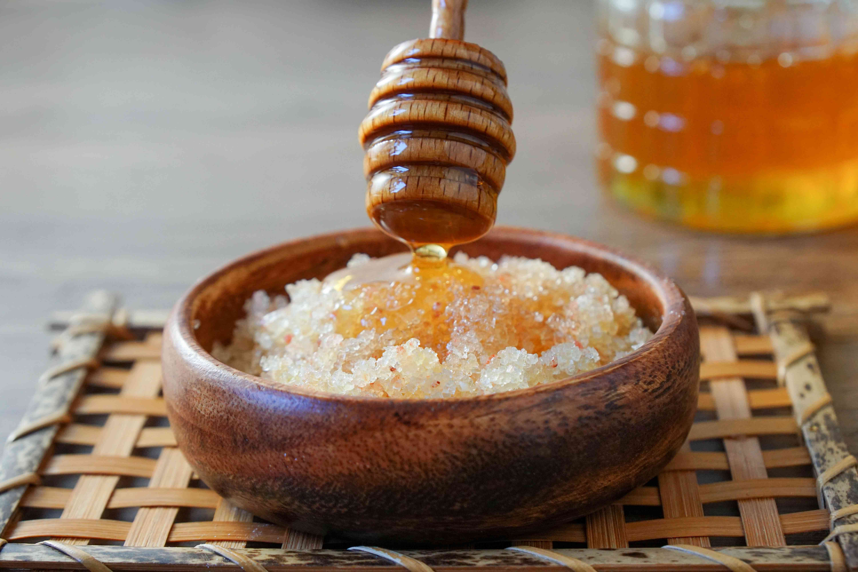 wooden honey dipper drizzles honey into salt scrub mixture in wooden bowl