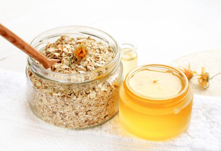 Glass jars of oatmeal flaks and yellow honey, white bathroom towel.