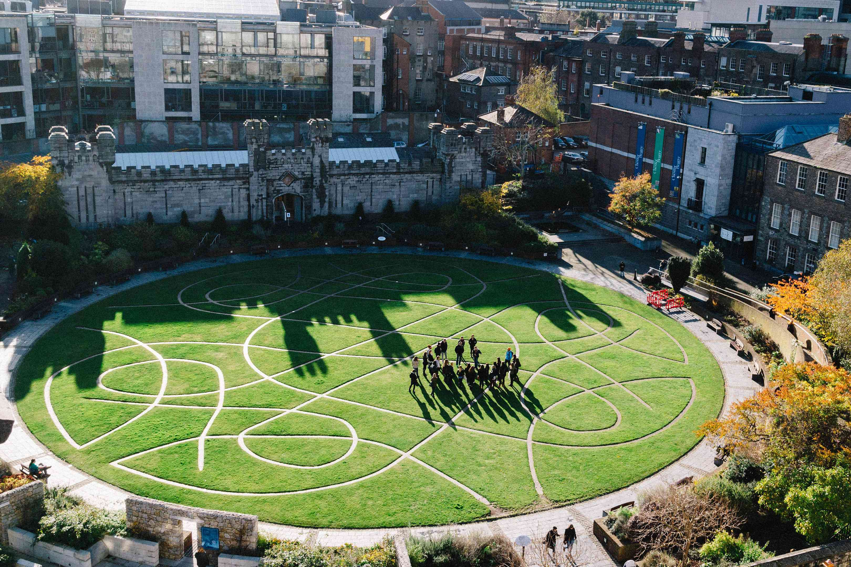 An overhead shot of a green lawn with a Celtic-inspired pattern of walkways