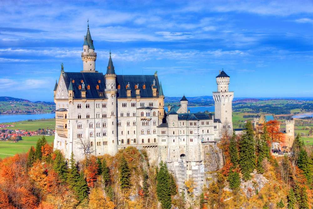 View of Neuschwanstein Castle surrounded by trees in autumn shades of red, orange, and yellow, under a clear blue sky with fields of grass and a river in the distance.