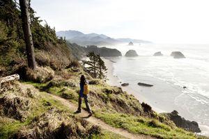 Hiker walking on a path overlooking the Oregon coast