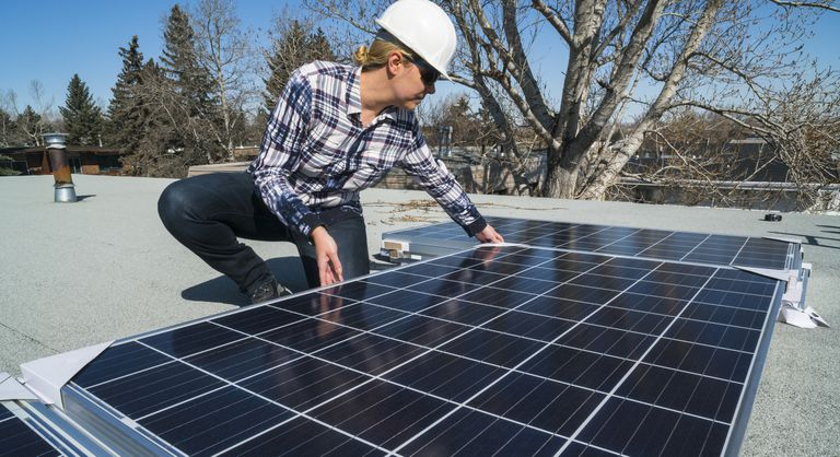 Female construction worker installing solar panels on a residential roof.