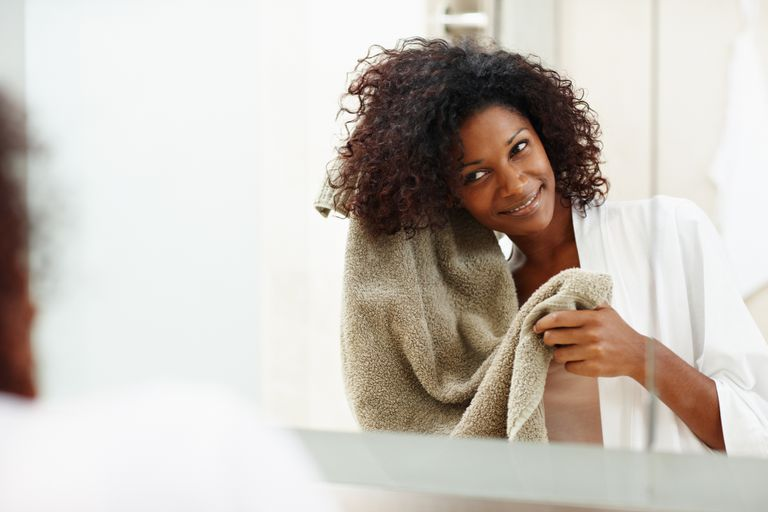 black woman drying her hair with a towel