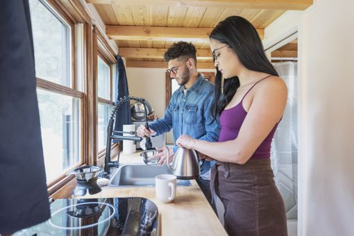Two people in a tiny house kitchen