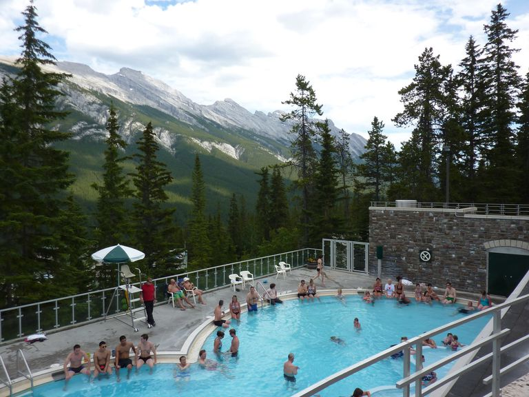 People enjoying the hot springs at Banff Upper Hot Springs with trees and mountains in the background