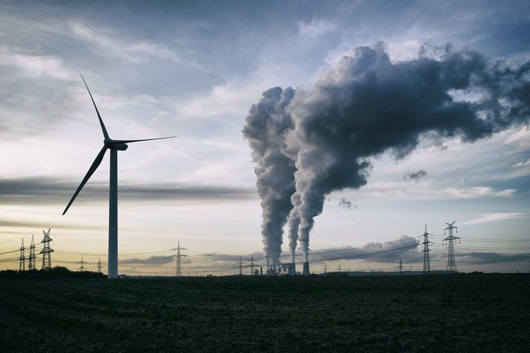 Single wind turbine and a coal burning power plant with pollution and electricity pylons in the background