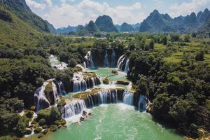 Multi-level Ban Gioc–Detian Falls surrounded by lush, green scenery and falls flowing into clear, green water