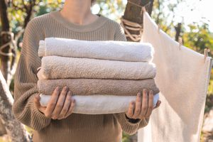 woman holds stack of towels outside