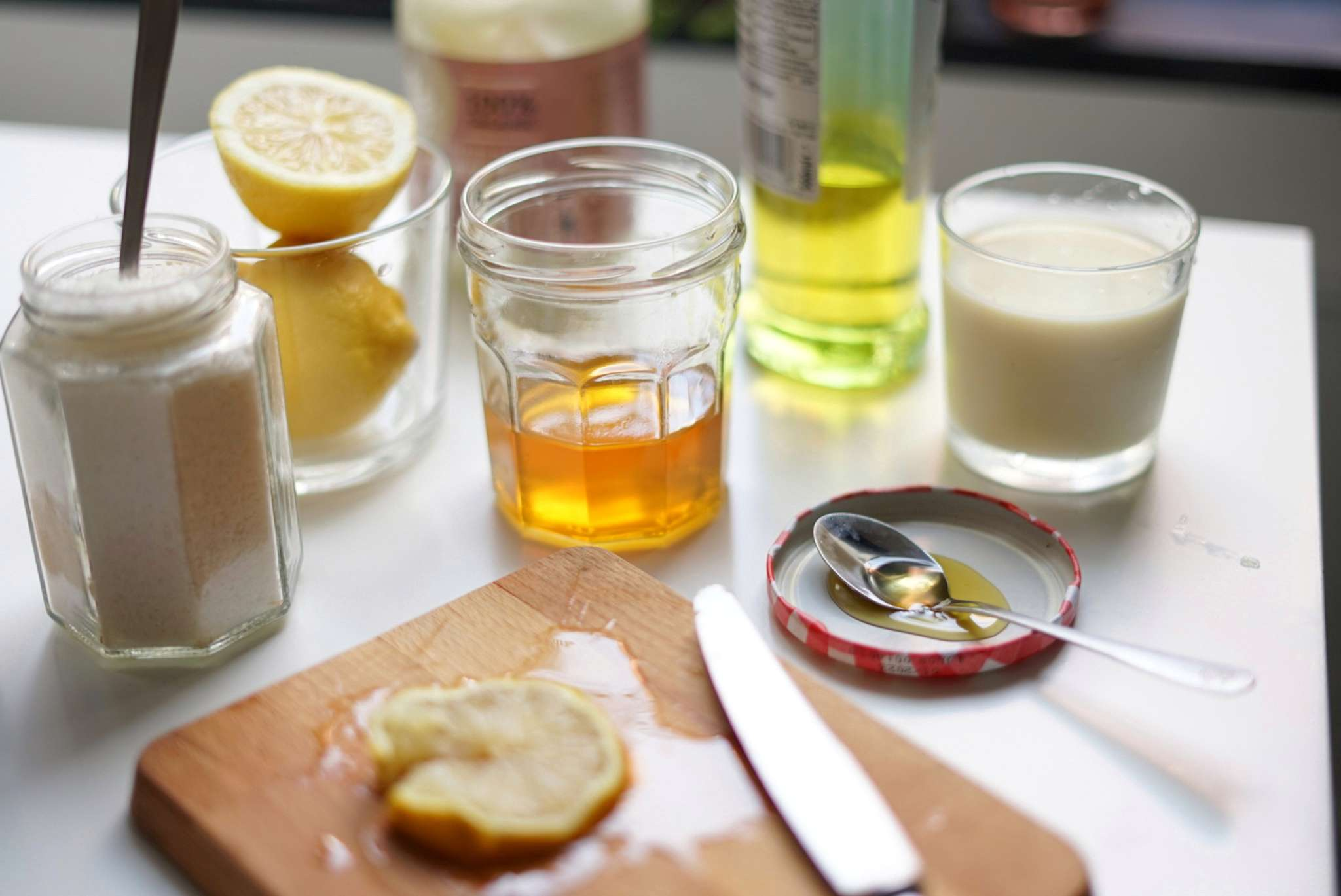 honey, cut lemons, milk, and ground almonds on table for natural beauty treatment