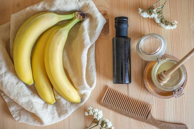 flat lay of bananas, small olive oil, honey in glass jar with dipper, and comb on table