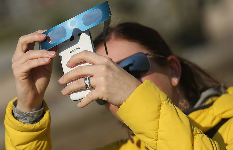 A woman uses special glasses and a smartphone to photograph a partial solar eclipse near the Brandenburg Gate on March 20, 2015 in Berlin, Germany.