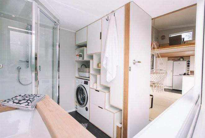 Bathroom showing storage cupboards and washing machine