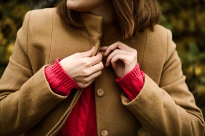 Woman buttoning coat