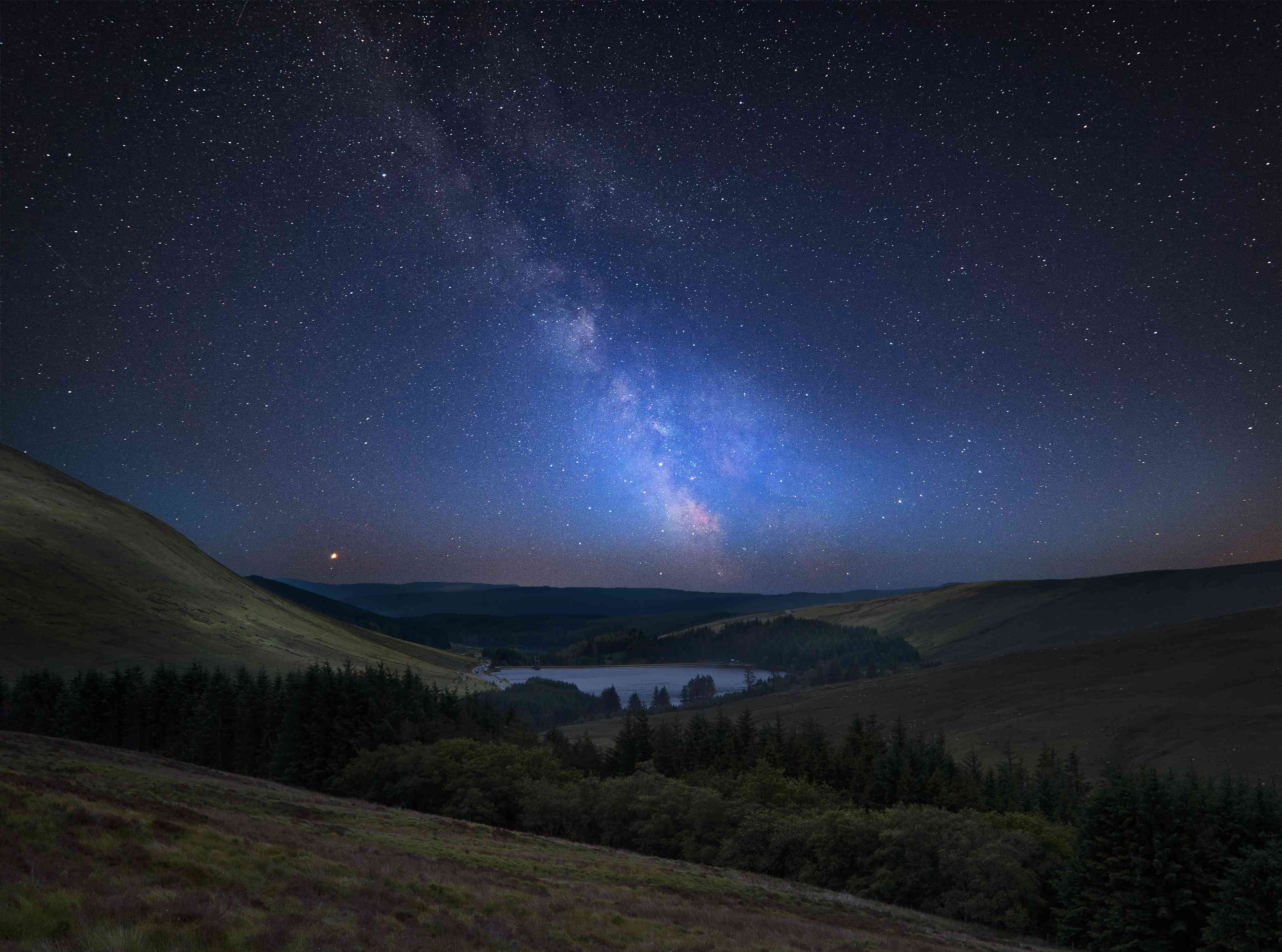 Milky Way over lush valley and mountains in the distance