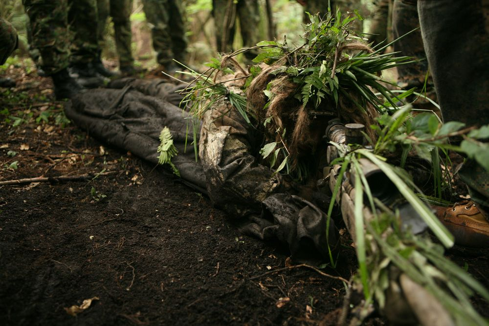 human lying on dirt ground covered in leaves as camouflage