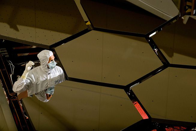 A technician inspects the mirror panels of the James Webb Space Telescope