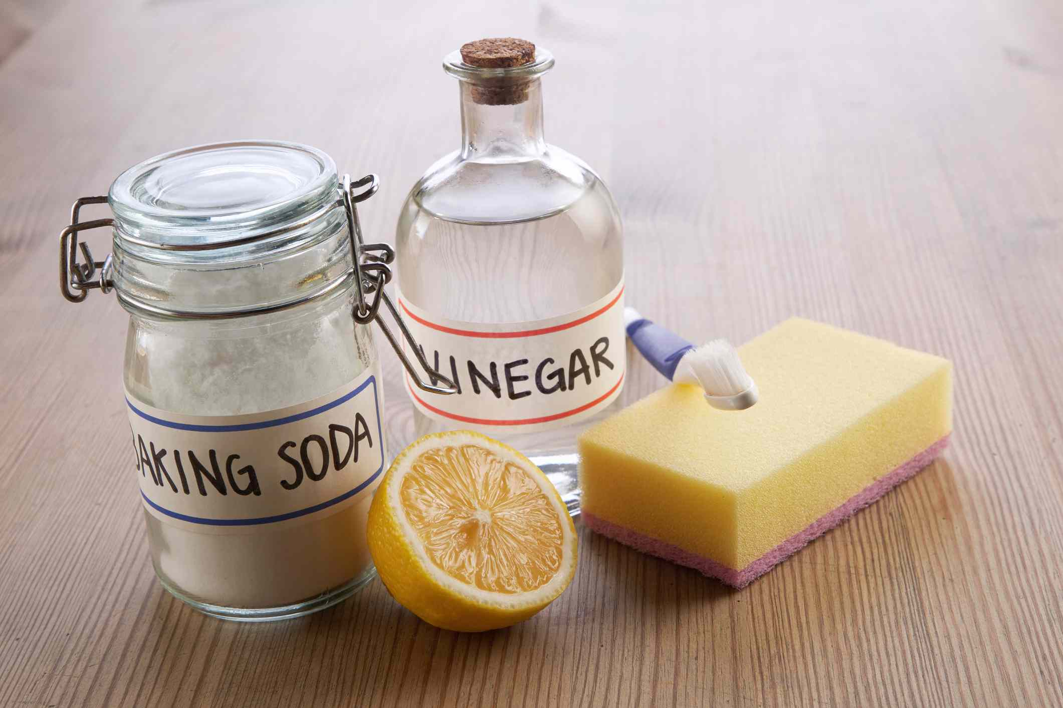 Vinegar, baking soda and cleaning products on a wood table.
