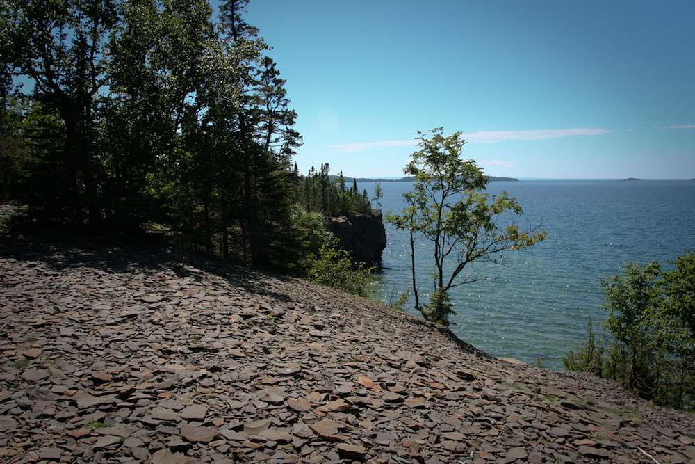 Silver Islet at Sleeping Giant Provincial Park, with trees and rocks on the shoreline and Lake Superior in the background under a blue sky
