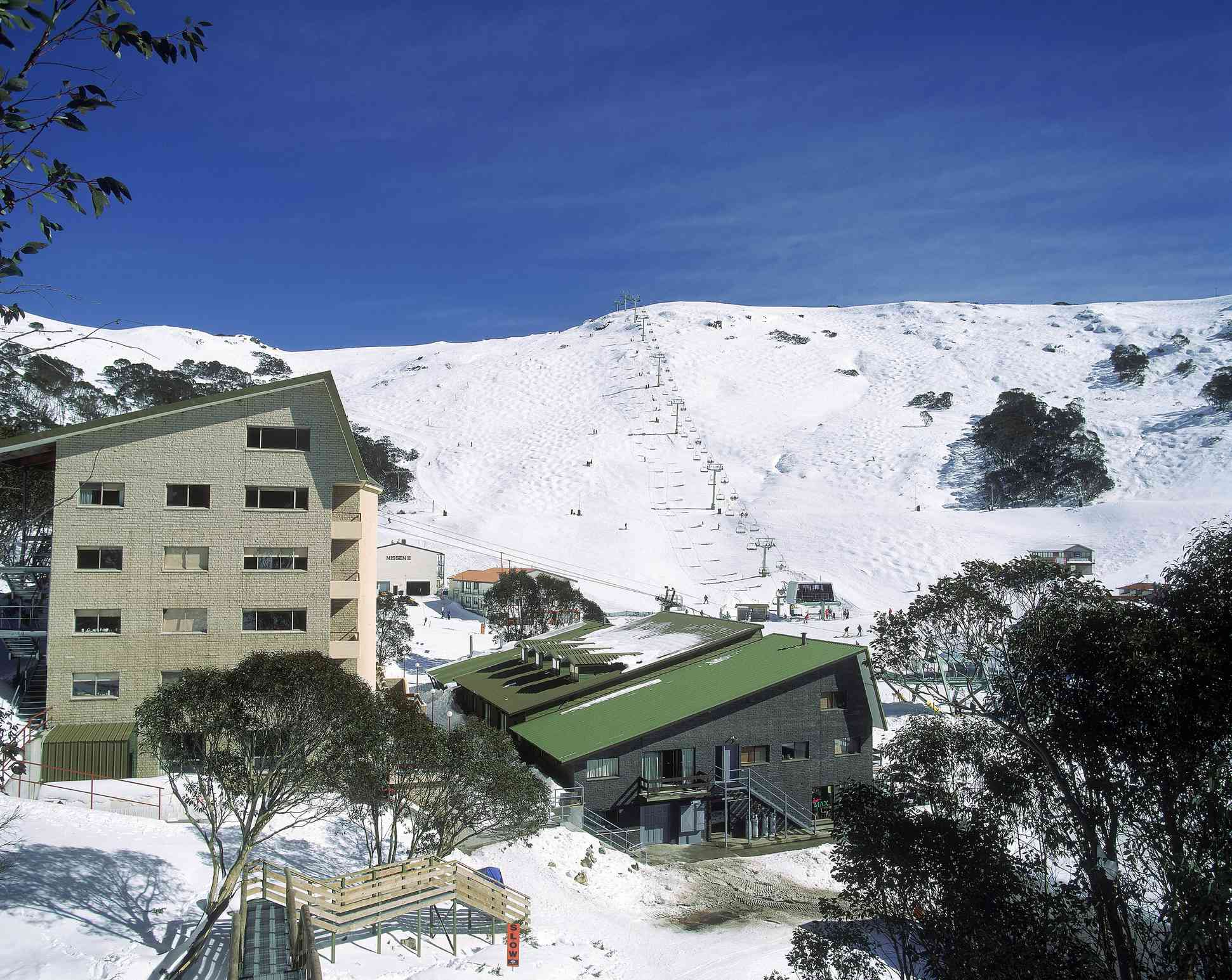 ski village at Falls Lake with midrise condominium building, ski lodge with a green sloped roof, and snow-covered ski slope below blue sky
