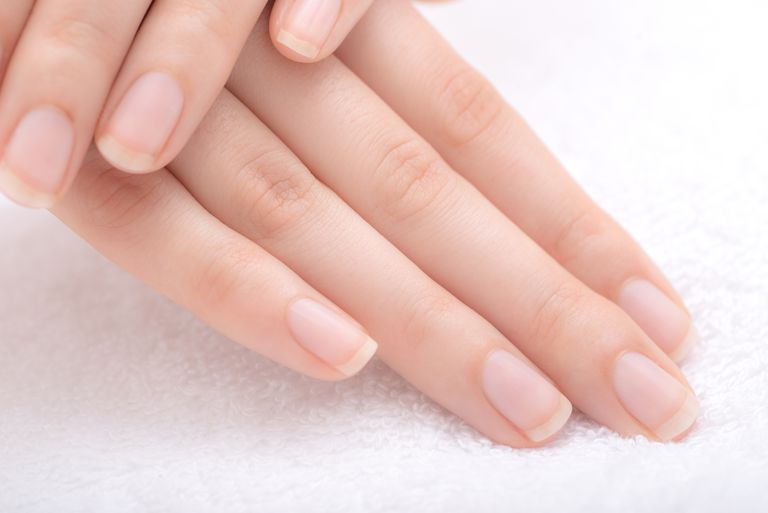 Healthy natural nails on a white towel.