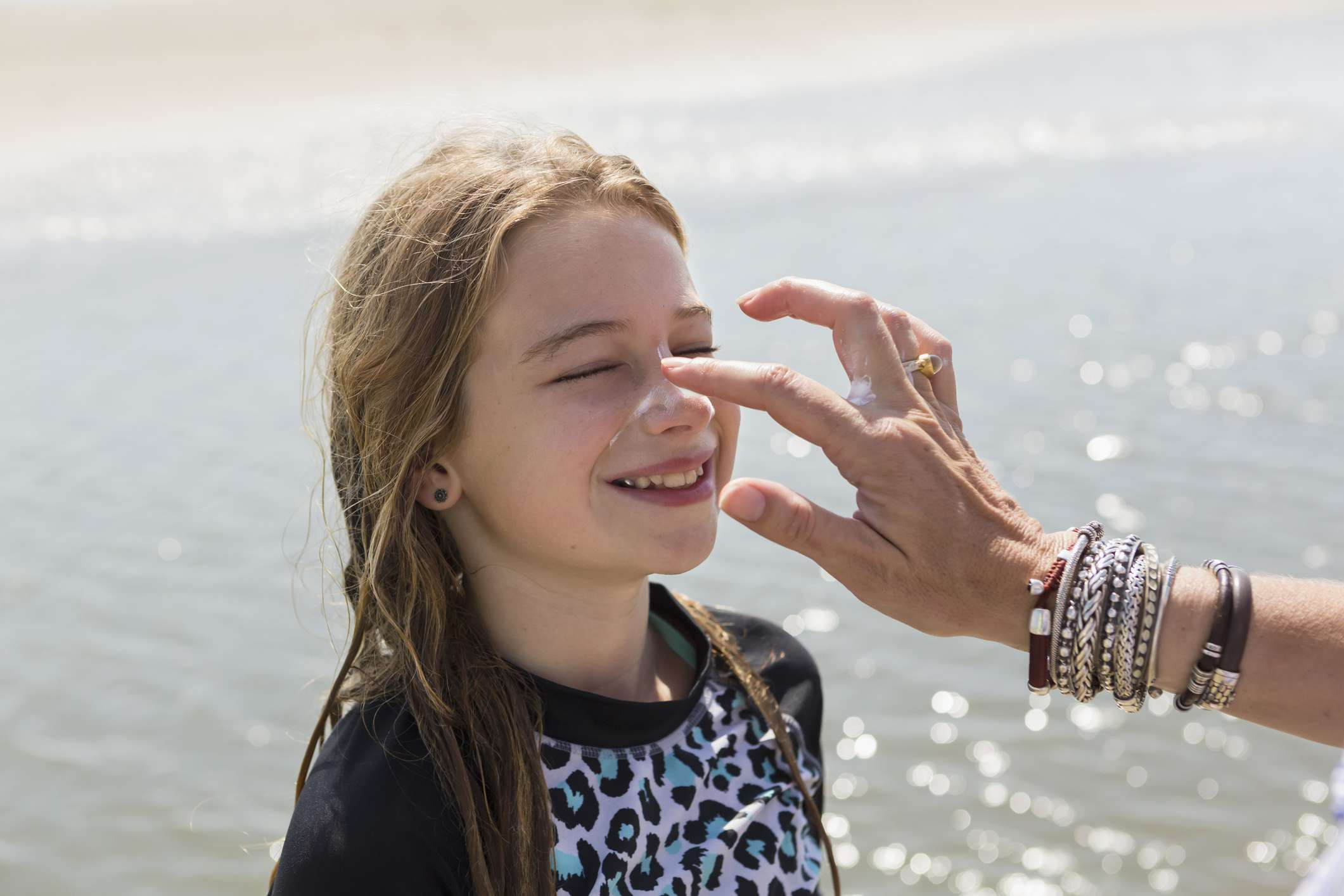 An adult with bracelets applies sunscreen on a white girl's face at the beach.