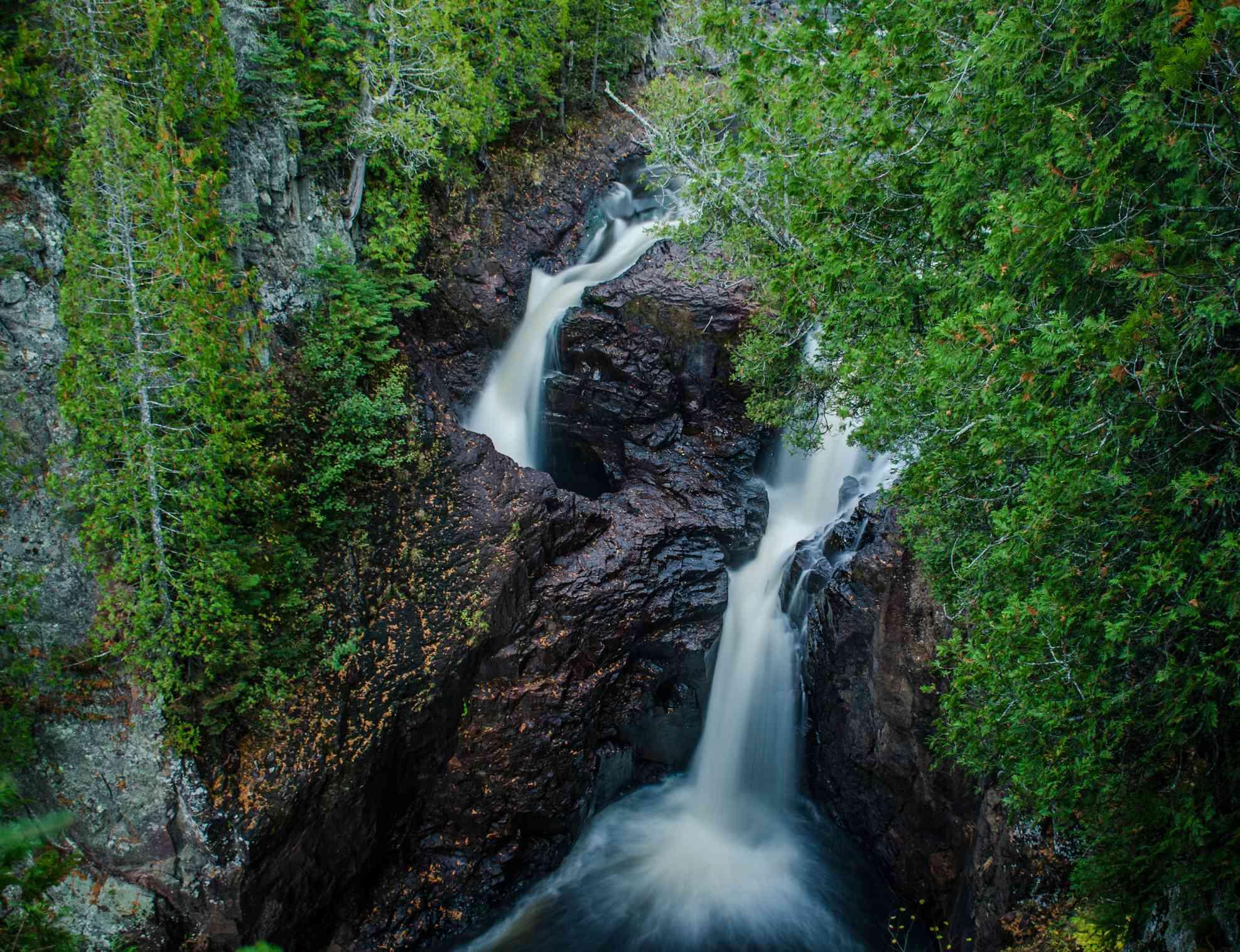 Twin waterfalls flow in a forest landscape