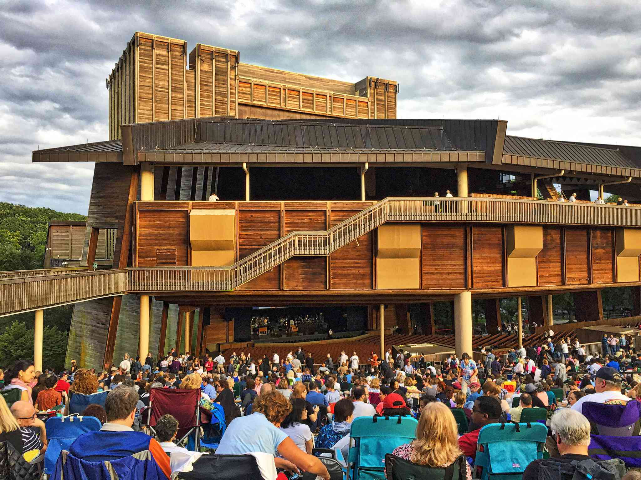 Daytime view of the audience seated in front of the Filene Center, a two story wooden structure and performance venue at Wolf Trap National Park