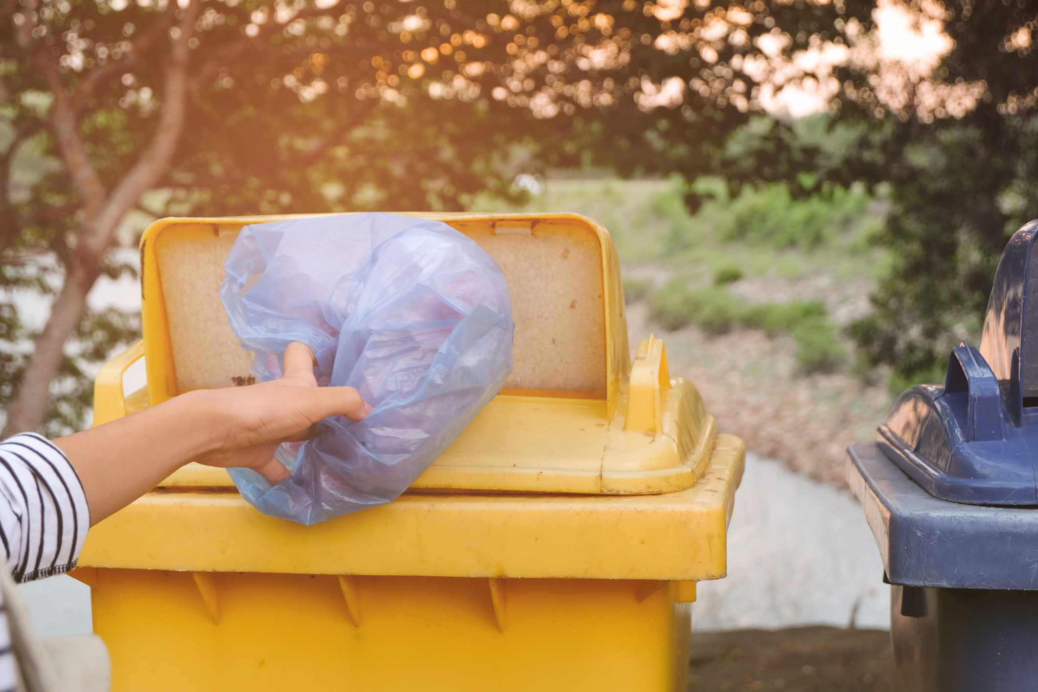 Person putting plastic bag in yellow recycling bin.