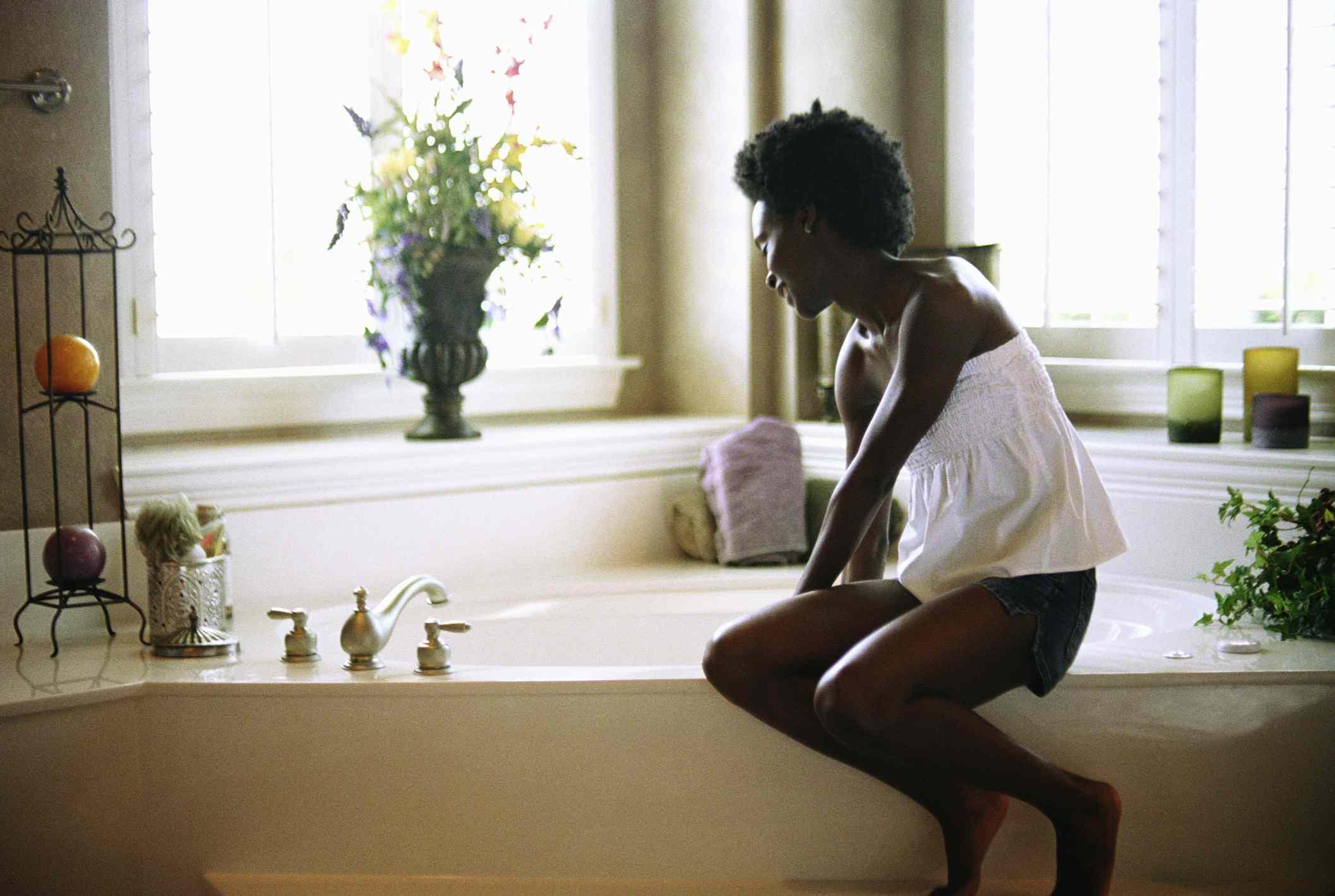 A black woman drawing a bath.