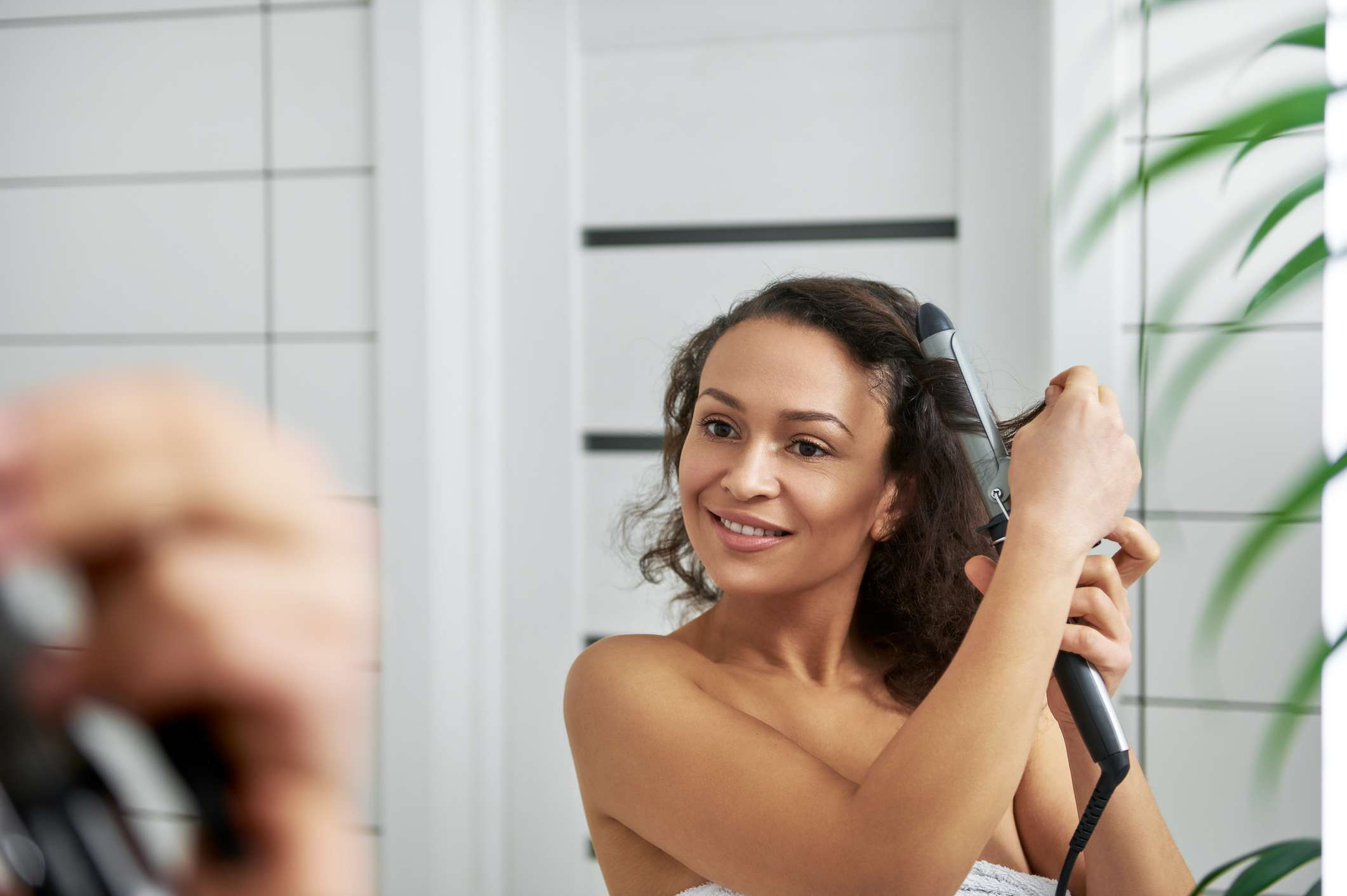 A light skinned black woman curling her hair in the mirror.