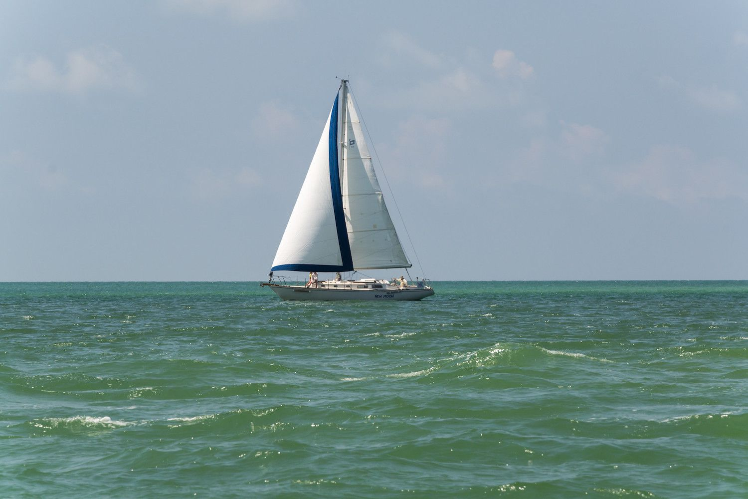 A sailboat on the greenish waters of the Gulf of Mexico off shore of North Captiva Island