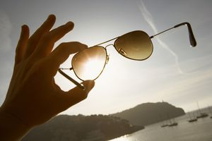 Holding sunglasses in the sun