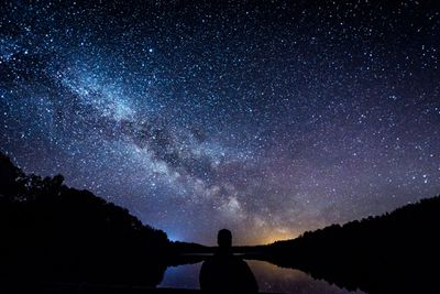 Dark silhouette of a human in the middle of a starry night sky and darkened hillsides