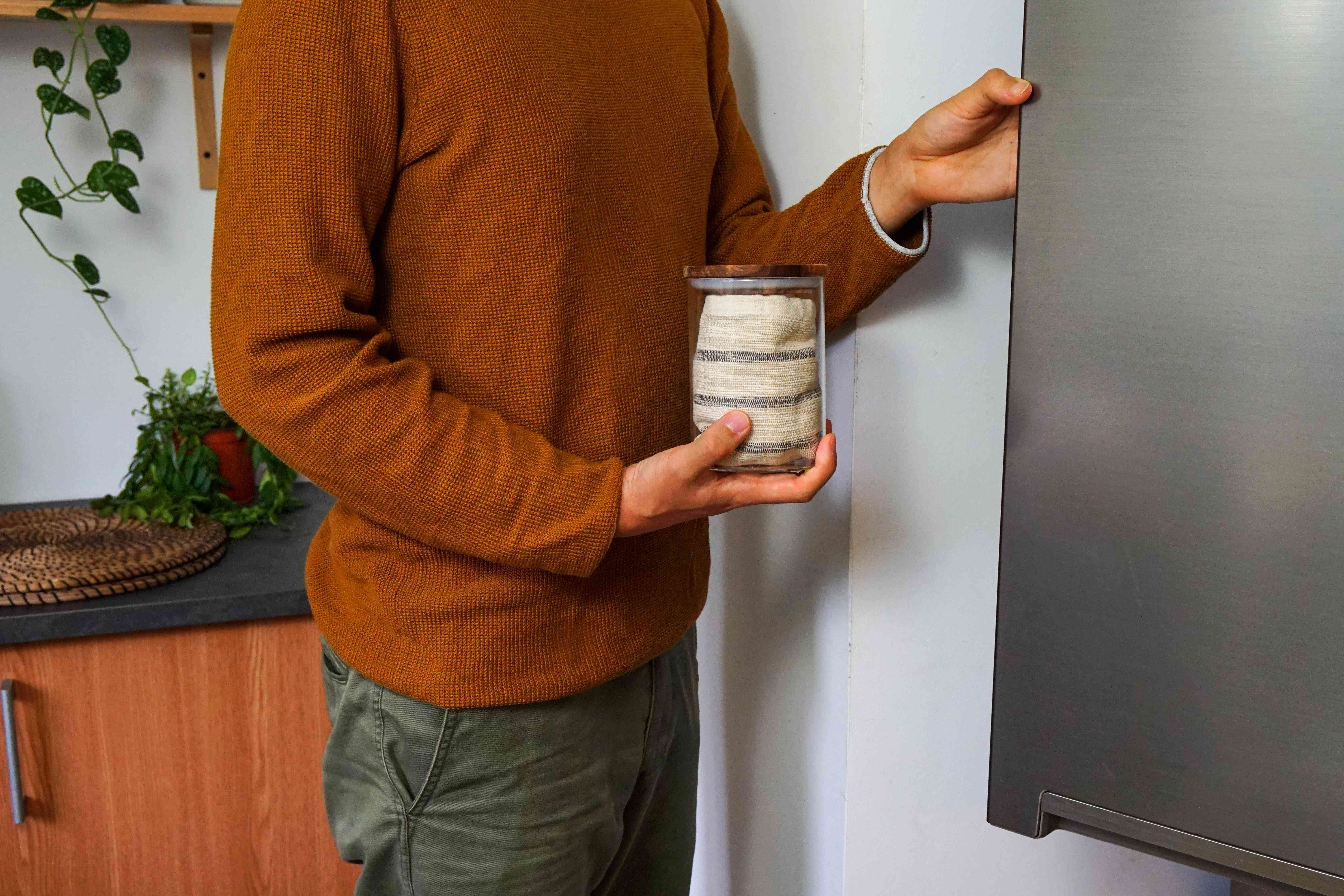 guy in rust-colored shirt places air-tight glass container full of fresh parsley in fridge