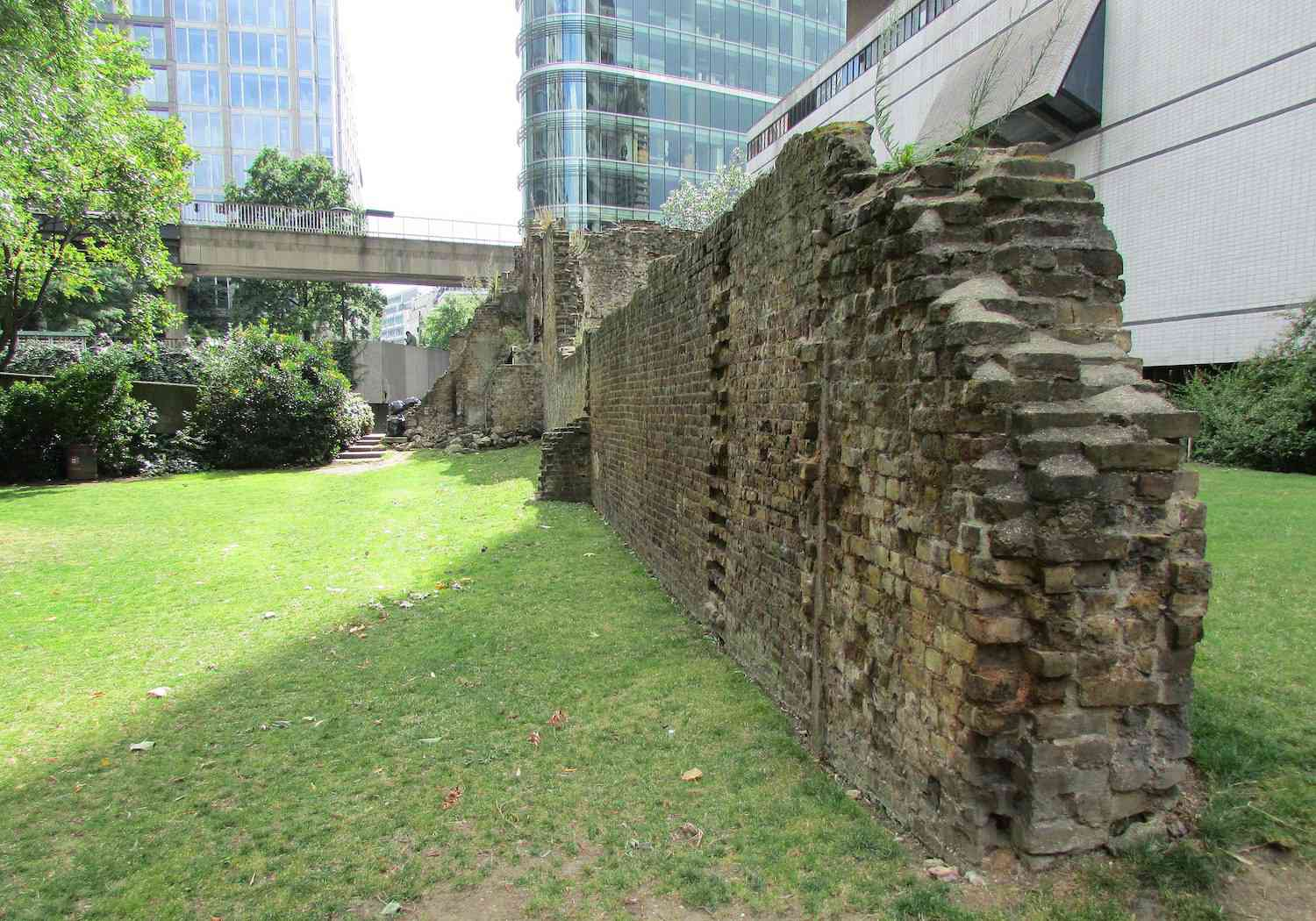 A portion of the Roman London Wall in front of skyscrapers