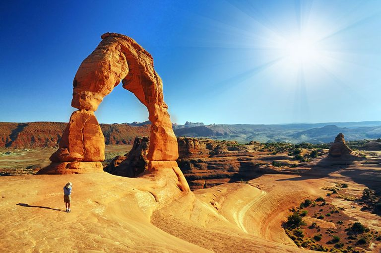 A natural arch with the sun shining bring behind it