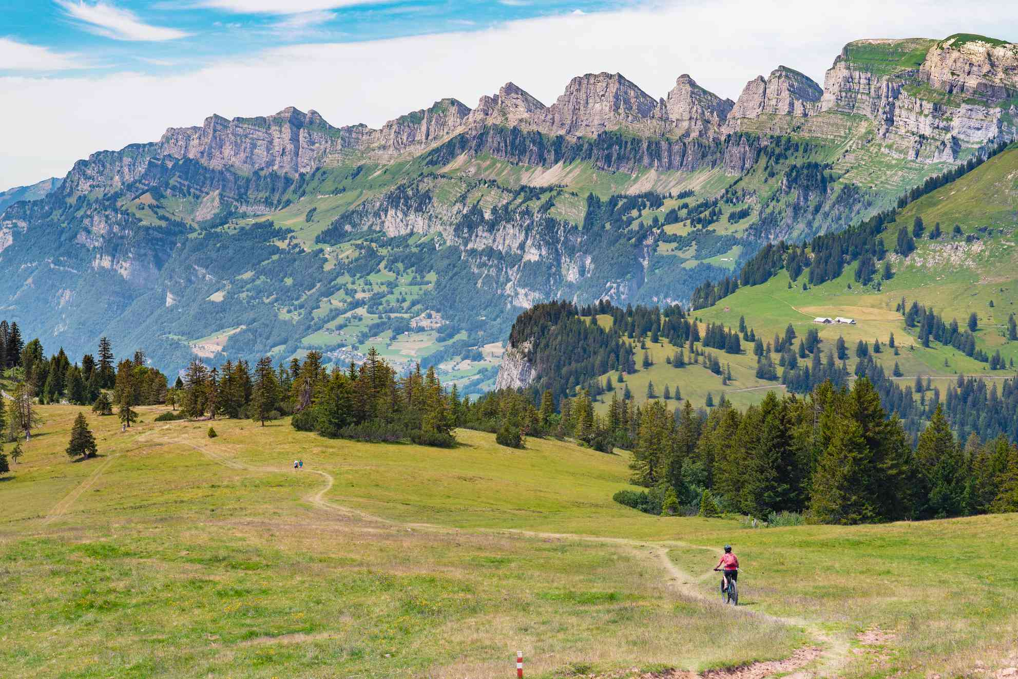 A woman on a mountain bike descends a trail in the Alps